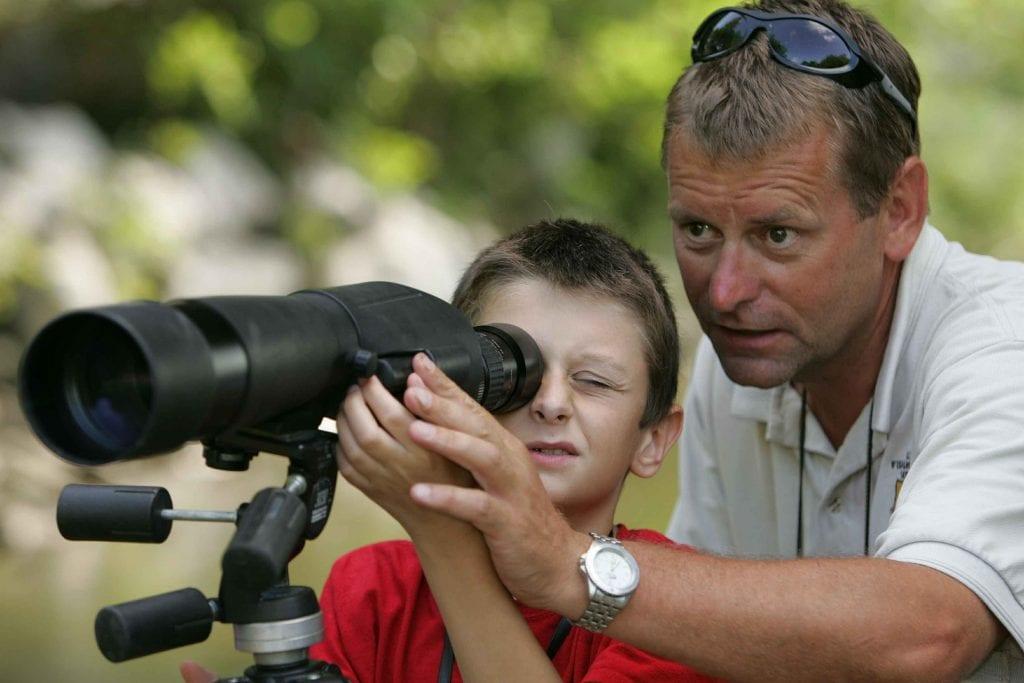 מבוגר עוזר לילד להשתמש בטלסקופ