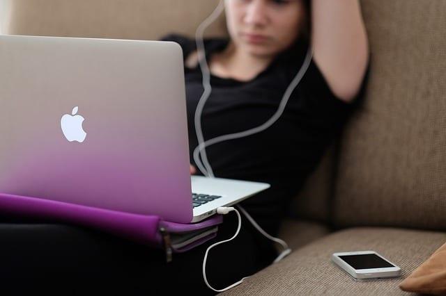 נערה עם אוזניות ומחשב של אפל